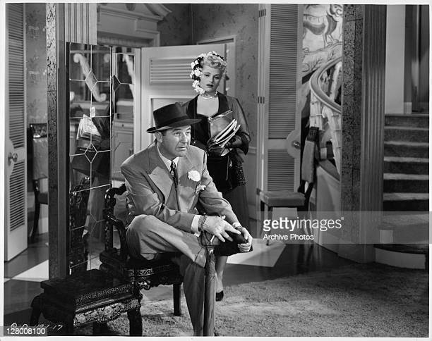 Broderick Crawford sitting and holding his shoe while Judy Holliday stands behind him in a scene from the film 'Born Yesterday' 1950