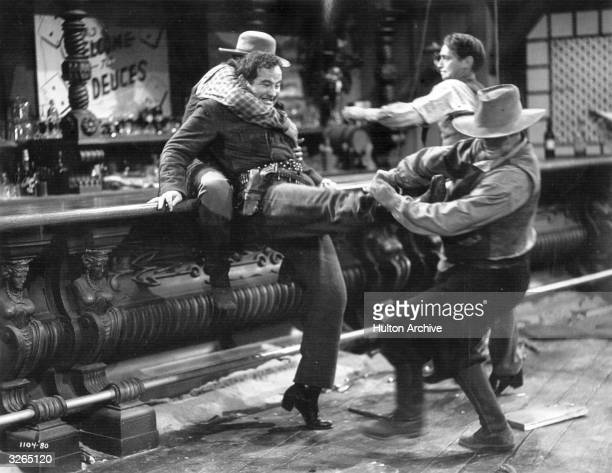 Broderick Crawford the American character actor engages in a saloon bar brawl with Franchot Tone in a scene from the film 'Trail Of The Vigilantes'...