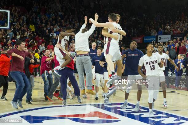 Brodeur Max Rothschild and Eddie Scott of the Pennsylvania Quakers celebrate their win against the Villanova Wildcats at The Palestra on December 11...