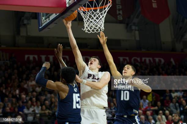 Brodeur of the Pennsylvania Quakers shoots the ball against Saddiq Bey and Cole Swider of the Villanova Wildcats at The Palestra on December 11 2018...