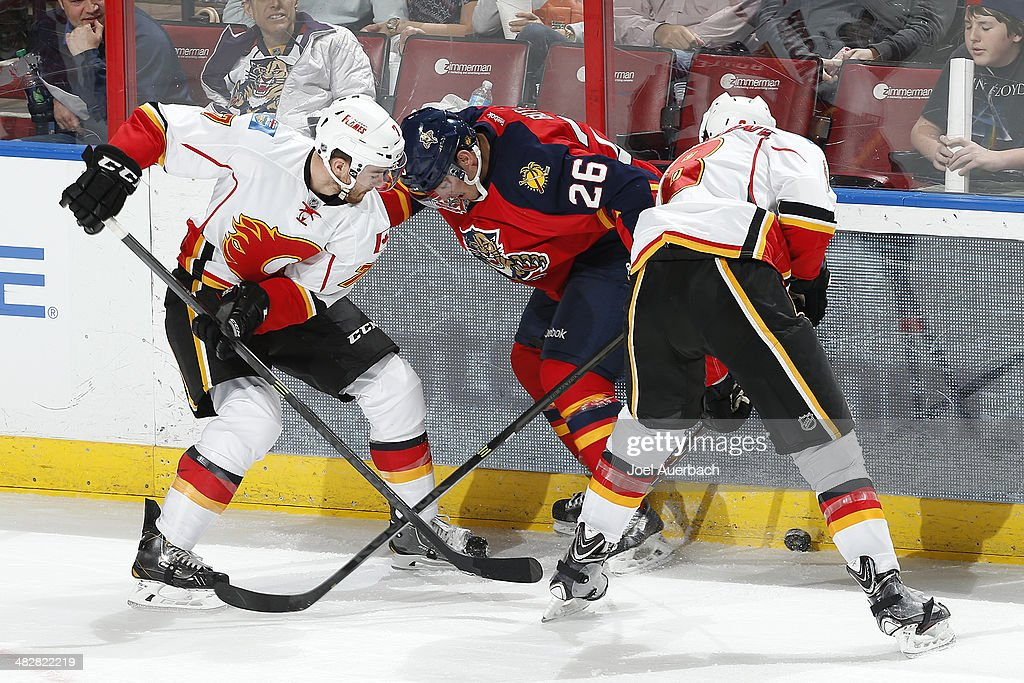 T.J. Brodie #7 and Joe Colborne #8 of the Calgary Flames check Bobby Butler #26 of the Florida Panthers off the puck during third period action at the BB&T Center on April 4, 2014 in Sunrise, Florida. The Flames defeated the Panthers 2-1.