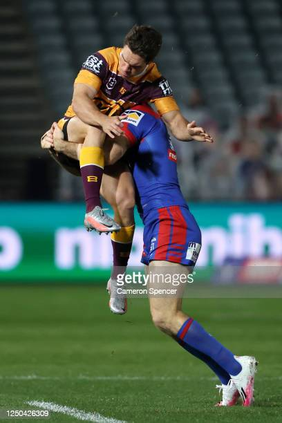 Brodie Croft of the Broncos is tackled in the air during the round six NRL match between the Newcastle Knights and the Brisbane Broncos at Central...