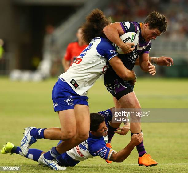 Brodie Croft of the Storm gets tackled during the round one NRL match between the Canterbury Bulldogs and the Melbourne Storm at Optus Stadium on...