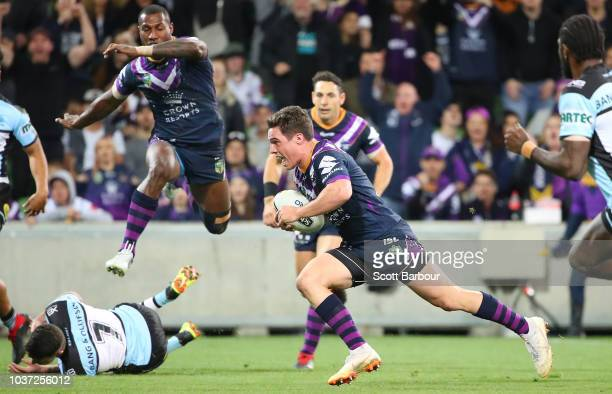 Brodie Croft of the Storm scores a try as Suliasi Vunivalu of the Melbourne Storm jumps during the NRL Preliminary Final match between the Melbourne...