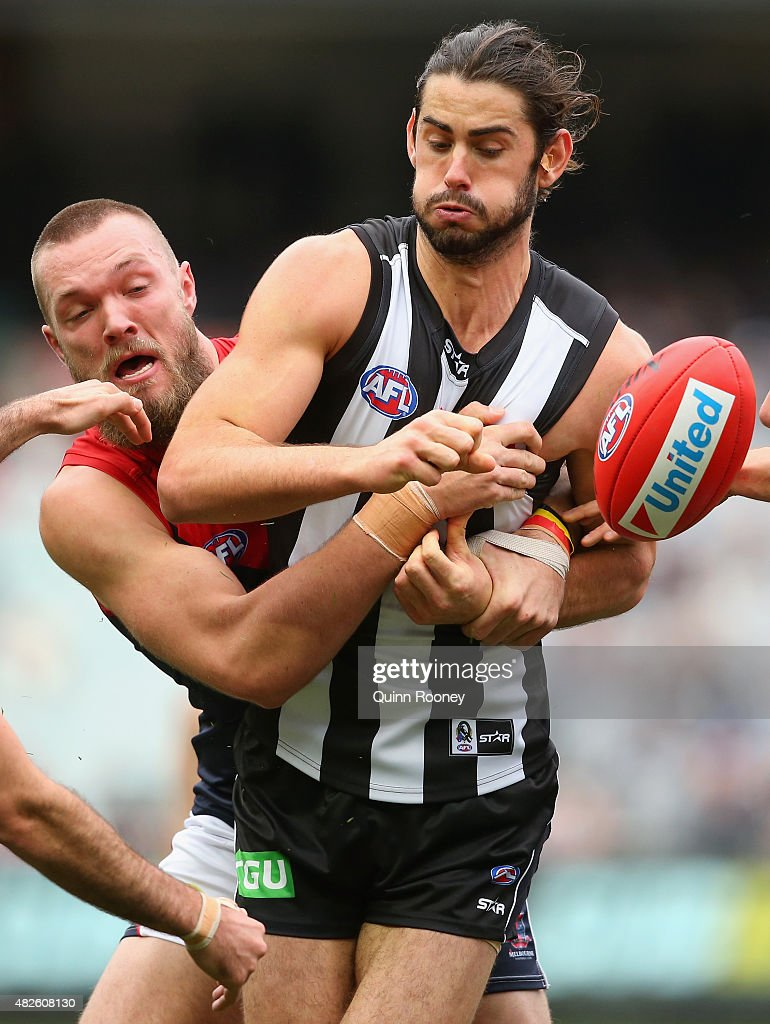Brodie Grundy of the Magpies handballs whilst being tackled by Max Gawn of the Demons during the round 18 AFL match between the Collingwood Magpies and the Melbourne Demons at Melbourne Cricket Ground on August 1, 2015 in Melbourne, Australia.
