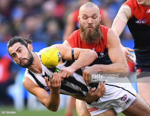 Brodie Grundy of the Magpies handballs whilst being tackled by Max Gawn of the Demons during the round 12 AFL match between the Melbourne Demons and...