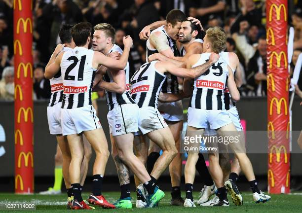 Brodie Grundy of the Magpies is congratulated by team mates after kicking a goal during the AFL Preliminary Final match between the Richmond Tigers...