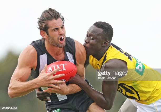 Brodie Grundy of the Magpies is tackled by Mabior Chol of the Tigers during the 2017 JLT Community Series AFL match between the Richmond Tigers and...