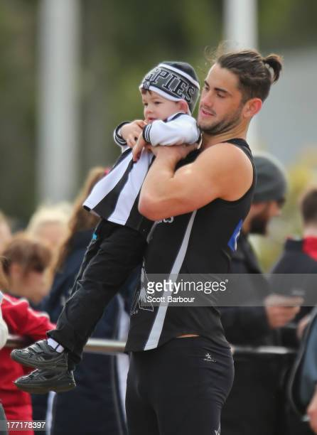 Brodie Grundy of the Magpies poses for a photo with a young supporter during a Collingwood Magpies AFL training session at Olympic Park on August 22...