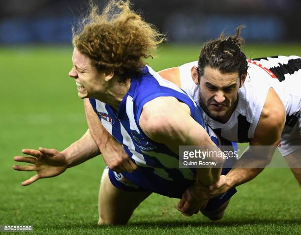 Brodie Grundy of the Magpies tackles Ben Brown of the Kangaroos during the round 20 AFL match between the North Melbourne Kangaroos and the...