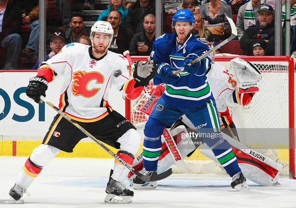 TJ Brodie #7 of the Calgary Flames and Henrik Sedin #33 of the Vancouver Canucks watch a shot during their NHL game at Rogers Arena January 10, 2015 in Vancouver, British Columbia, Canada.