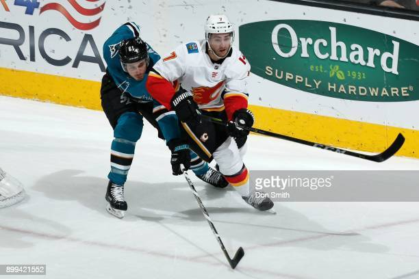 Brodie of the Calgary Flames and Justin Braun of the San Jose Sharks chase the puck at SAP Center on December 28 2017 in San Jose California