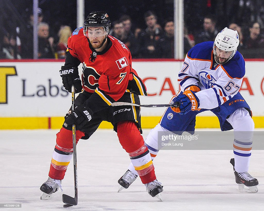 T.J. Brodie #7 of the Calgary Flames carries the puck against Benoit Pouliot #67 of the Edmonton Oilers during an NHL game at Scotiabank Saddledome on January 31, 2015 in Calgary, Alberta, Canada. The Flames defeated the Oilers 4-2.