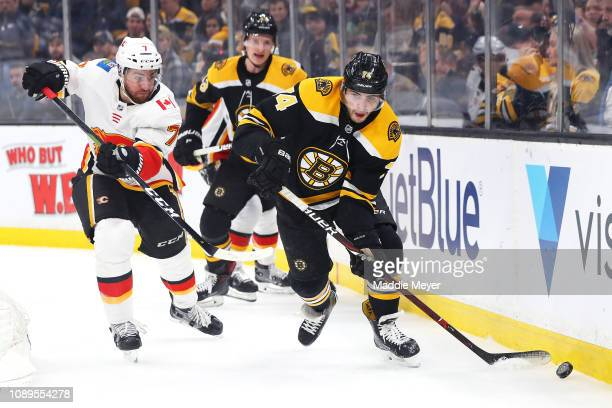 Brodie of the Calgary Flames defends Jake DeBrusk of the Boston Bruins during the game between the Boston Bruins and Calgary Flames at TD Garden on...