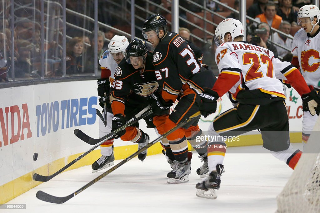 T.J. Brodie #7 of the Calgary Flames, Dougie Hamilton #27 of the Calgary Flames, Nick Ritchie #37 of the Anaheim Ducks, and Jakob Silfverberg #33 of the Anaheim Ducks battle for a loose puck during the third period of a game at Honda Center on November 24, 2015 in Anaheim, California.