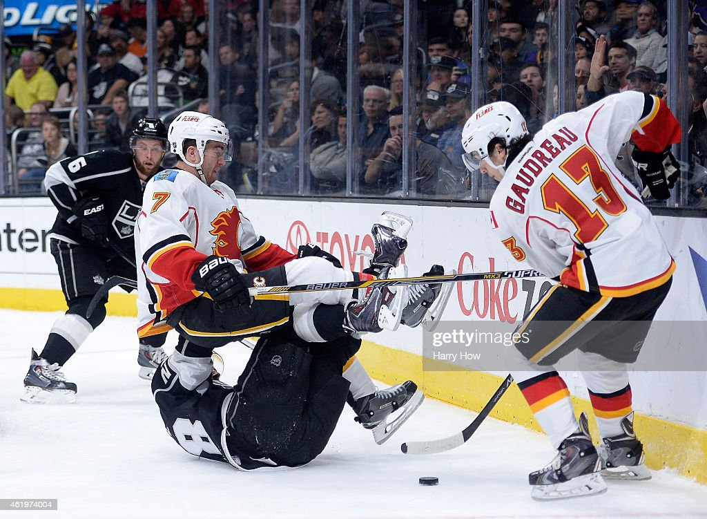 T.J. Brodie #7 of the Calgary Flames falls on top of Jarret Stoll #28 of the Los Angeles Kings as Johnny Gaudreau #13 stick handles around at Staples Center on January 19, 2015 in Los Angeles, California.
