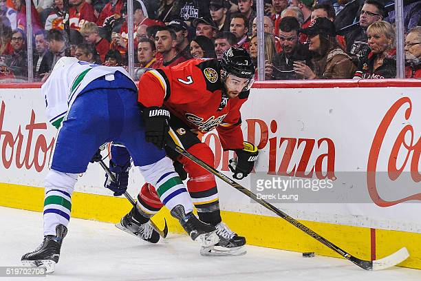 J Brodie of the Calgary Flames fights for the puck against Jannik Hansen of the Vancouver Canucks during an NHL game at Scotiabank Saddledome on...