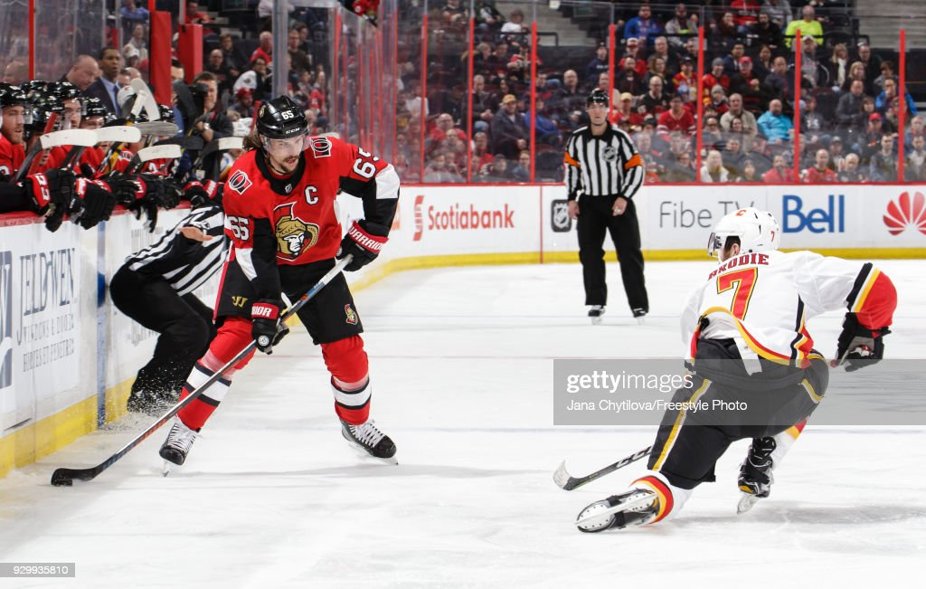 TJ Brodie #7 of the Calgary Flames goes down on a knee to successfully block a pass from Erik Karlsson #65 of the Ottawa Senators in the second period at Canadian Tire Centre on March 9, 2018 in Ottawa, Ontario, Canada.