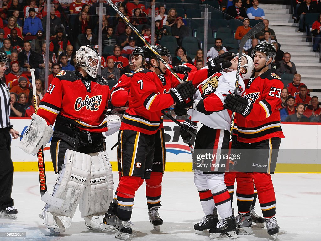 TJ Brodie #7 of the Calgary Flames roughs up Kyle Turris #7 of the Ottawa Senators at Scotiabank Saddledome on November 15, 2014 in Calgary, Alberta, Canada.