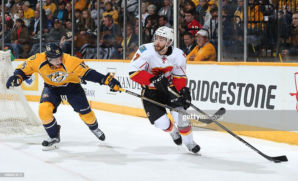 T.J. Brodie #7 of the Calgary Flames skates against Craig Smith #15 of the Nashville Predators during an NHL game at Bridgestone Arena on March 29, 2015 in Nashville, Tennessee.