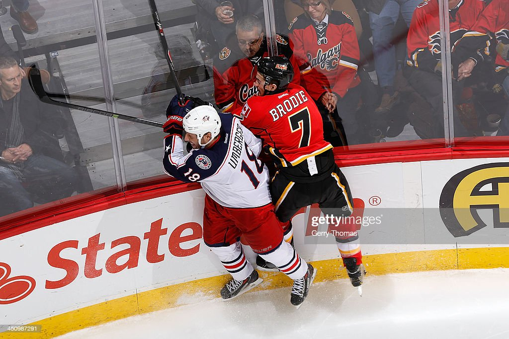T.J. Brodie #7 of the Calgary Flames skates against R.J. Umberger #18 of the Columbus Blue Jackets at Scotiabank Saddledome on November 20, 2013 in Calgary, Alberta, Canada.
