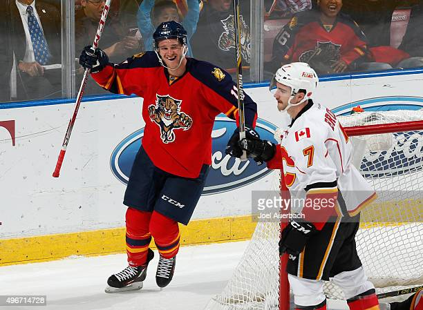J Brodie of the Calgary Flames skates away from the net as Jonathan Huberdeau raises his stick to celebrate the game winning goal by Jaromir Jagr of...