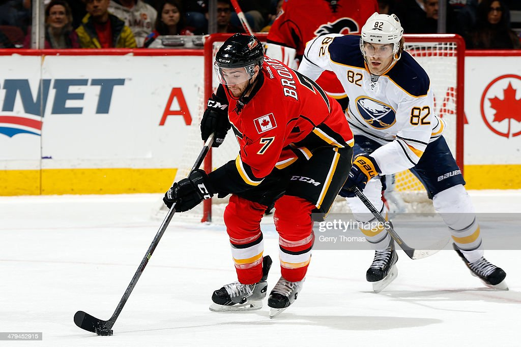 TJ Brodie #7 of the Calgary Flames skates the puck against Marcus Foligno #82 of the Buffalo Sabres at Scotiabank Saddledome on March 18, 2014 in Calgary, Alberta, Canada.