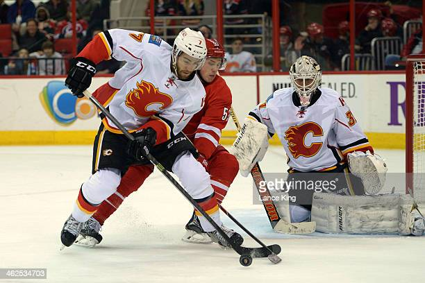 J Brodie of the Calgary Flames skates with the puck against Jeff Skinner of the Carolina Hurricanes at PNC Arena on January 13 2014 in Raleigh North...