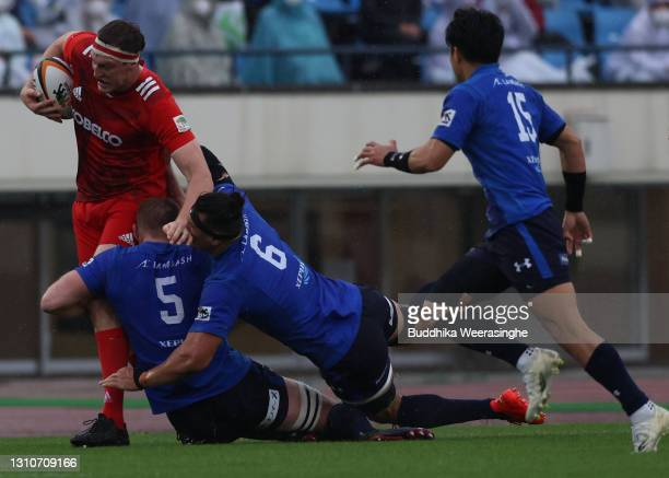 Brodie Retallick of Kobelco Steelers runs the ball against George Kruis and Ben Gunter of Panasonic Wild Knights during the Top League match between...