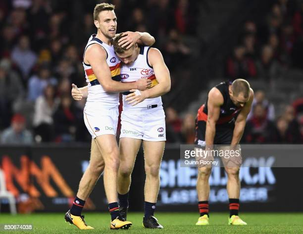 Brodie Smith of the Crows is congratulated by Rory Laird after kicking a goal during the round 21 AFL match between the Essendon Bombers and the...