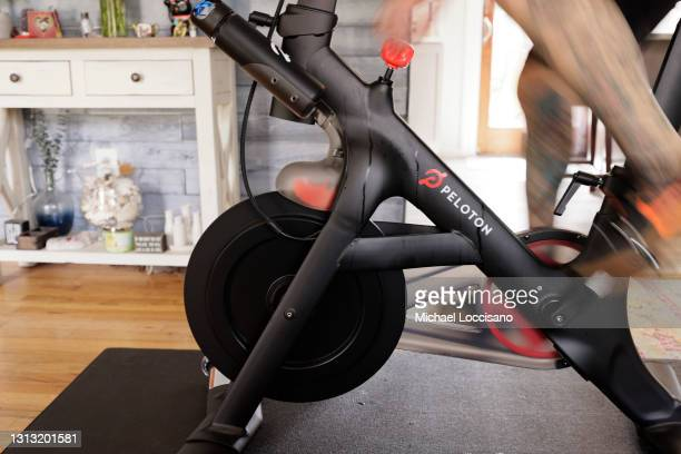 Brody Longo finishes a workout on his Peloton exercise bike on April 16, 2021 in Brick, New Jersey. There is a competitive business war between...