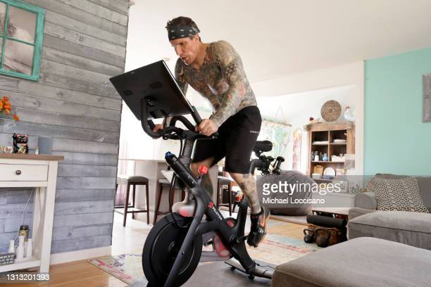 Brody Longo works out on his Peloton exercise bike on April 16, 2021 in Brick, New Jersey. There is a competitive business war between indoor...