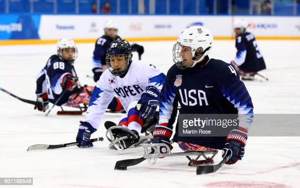 Brody Roybal of United States battles for the puck with Seung Ju Lee of Korea in the Ice Hockey Preliminary Round Group B game between United States...