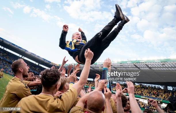 Broendby's players throw head coach Niels Frederiksen in the air as they celebrate winning the Danish Football Championship Superliga after the Super...
