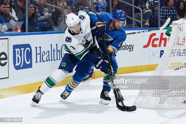 Brogan Rafferty of the Vancouver Canucks and Jaden Schwartz of the St Louis Blues battle for the puck at Enterprise Center on April 6 2019 in St...