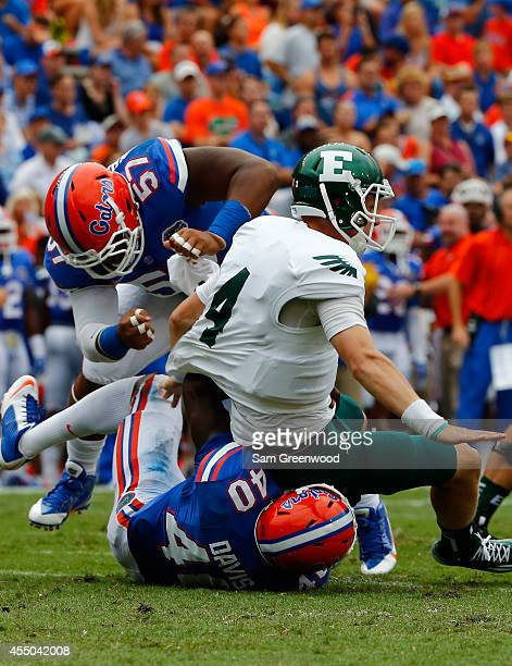 Brogan Roback of the Eastern Michigan Eagles is sacked by Jarrad Davis of the Florida Gators and Caleb Brantley during the game at Ben Hill Stadium...
