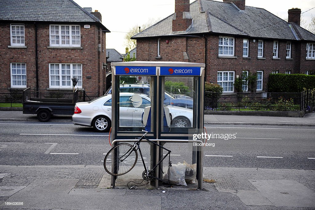 A broken and damaged bicycle sits locked outside two fixed-line public telephone booths, operated by Eircom Group, in Dublin, Ireland, on Thursday, May 24, 2013. Eircom Group, which has changed ownership six times since 1999, 'would like to be consolidators rather than consolidated' amid expected mergers and acquisitions in the Irish telecoms market, its Chief Financial Officer Richard Moat said. Photographer: Aidan Crawley/Bloomberg via Getty Images