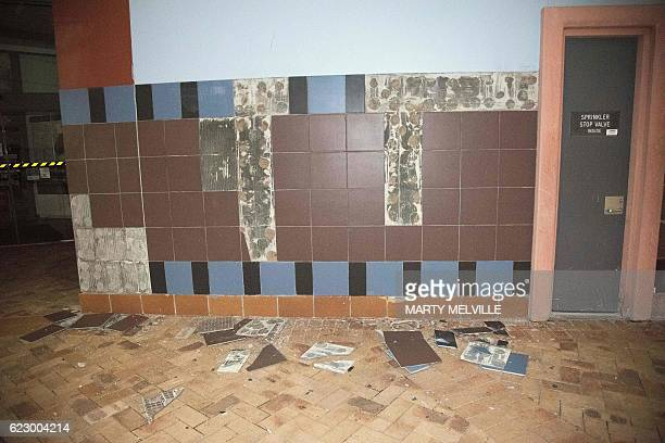 Broken and detached wall tiles are seen at the Wellington library early on November 14 2016 following an earthquake centred some 90 kilometres north...