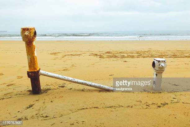 broken and rusty railing buried in the sand of the beach - ヒホン ストックフォトと画像