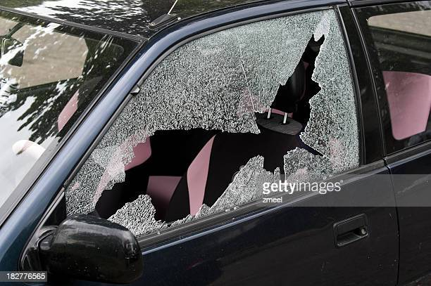 A broken and smashed window of a car in a driveway