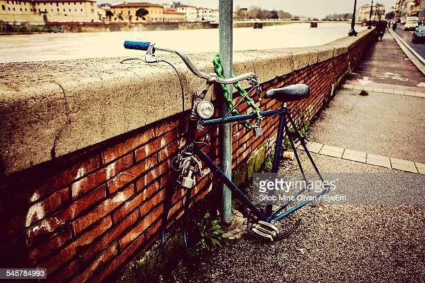 Broken Bicycle Parked By Retaining Wall On Street