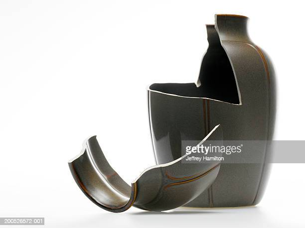Broken black vase against white background (still life)