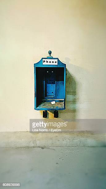 Broken Blue Pay Phone On Wall