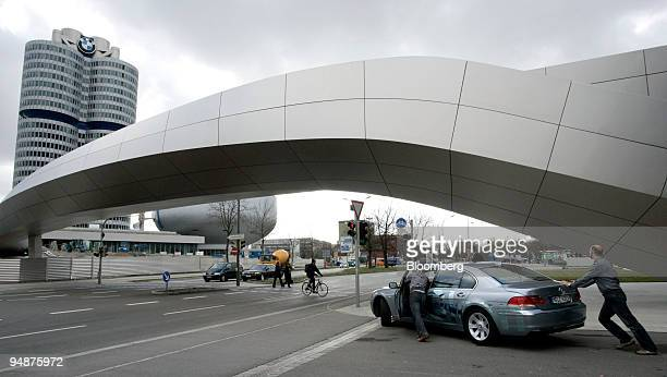 A broken BMW automobile is pushed past the BMW Group headquarters prior to the the company's 2007 results news conference in Munich Germany on...