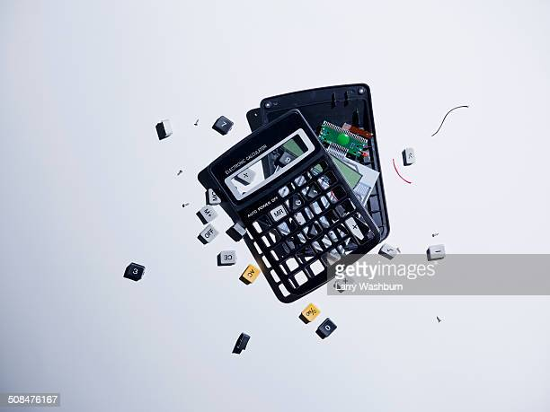 broken calculator against gray background - calculator stock photos and pictures