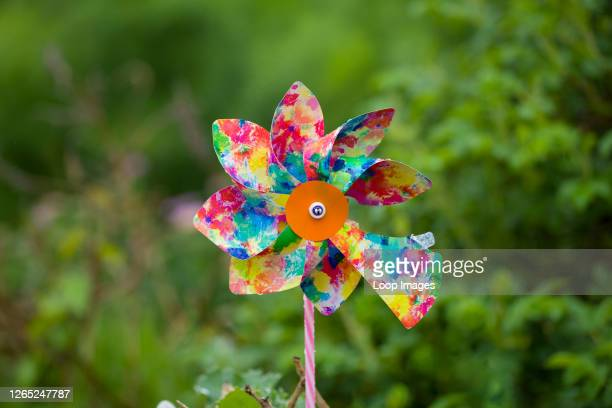 Broken child's windmill against a blurred background of foliage.