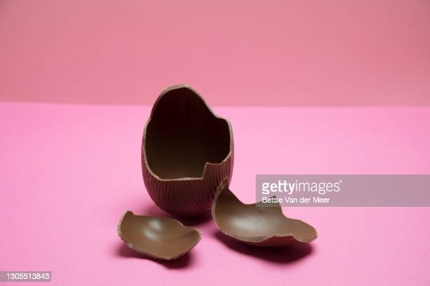 broken chocolate easter egg on pink background. - イースターエッグのチョコレート ストックフォトと画像
