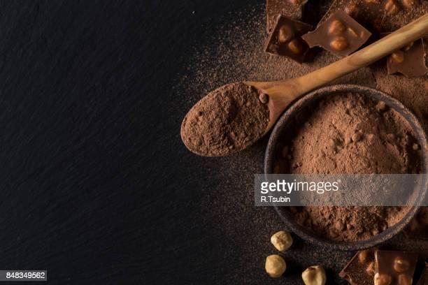 Broken chocolate nuts pieces and cocoa powder