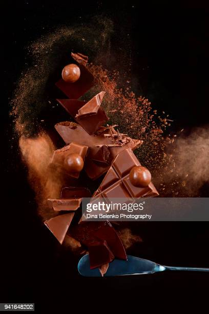 broken chocolate pieces balancing on a tip of a dessert knife with cocoa powder explosion in motion. chocolate dust on a black background. action food photography. - chocolate stock pictures, royalty-free photos & images