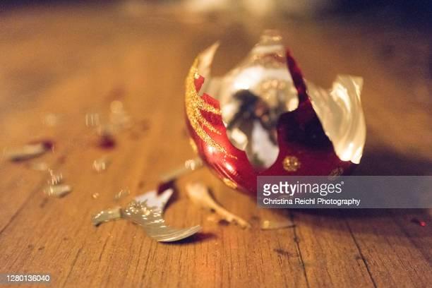 broken christmas bauble on floor - christina grosse stock-fotos und bilder